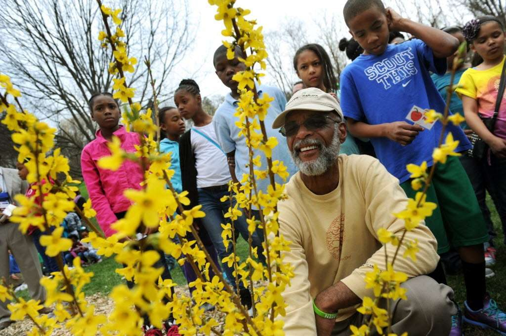 Yusuf Burgess of Ed-Venture and Nature Network, center, is seen helping to plant forsythia in a new schoolyard garden on Tuesday, April 22, 2014, at Arbor Hill Elementary in Albany, N.Y. (Cindy Schultz / Times Union)