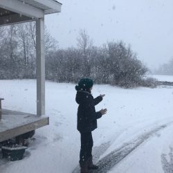 picture of a child in snowstorm catching snowflakes