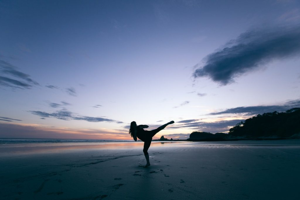 Picture of a person kicking the air on a beach.