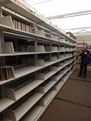 a man stands next to metal library shelves