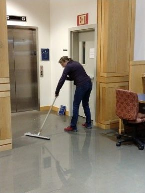 Science Data Librarian Wendy Shook mops the floor in Armstrong Library, Middlebury College