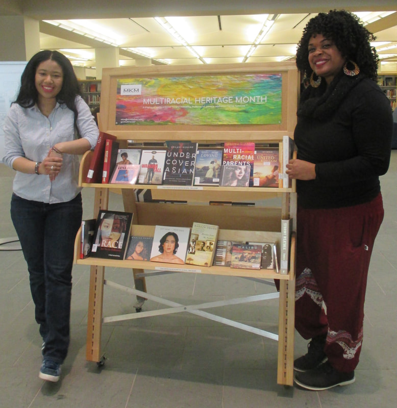 two women pose with a book cart