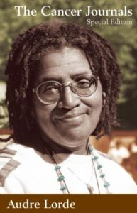 A headshot of Audre Lorde wearing glasses and a necklace