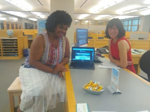 Two librarians seated at the Davis Family Library Research Desk, one using a stool