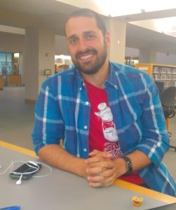 Middlebury College Assistant Professor of Spanish and Linguistics Marcos Rohena-Madrazo, born and raised in Puerto Rico, poses for a photo at the Davis Family Library Research Desk.
