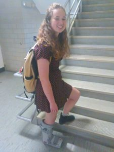 A young woman wearing a medical boot poses on a flight of stairs.