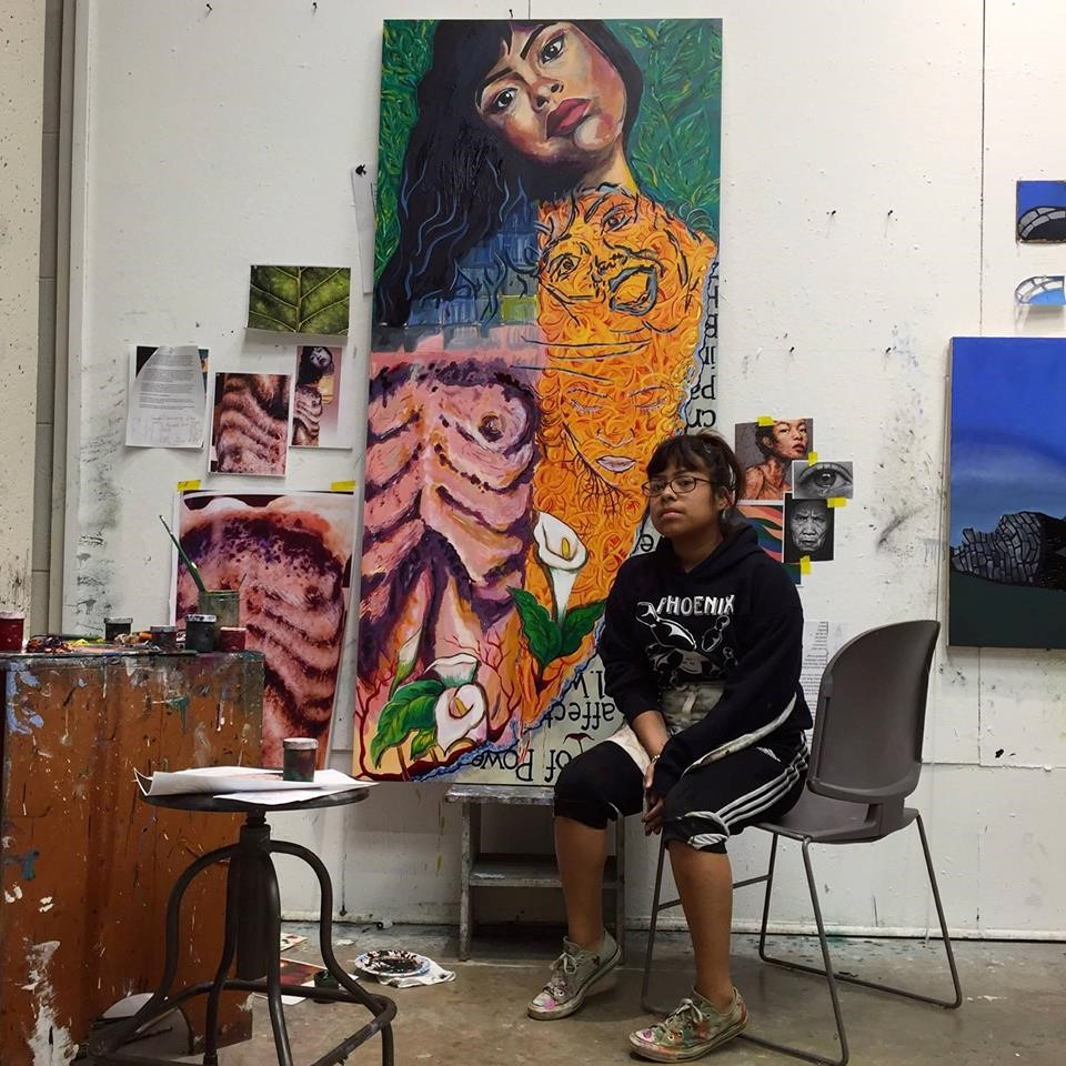 Zarai Zaragoza, a Mexican American Middlebury College senior and studio art major sits in front of colorful art pieces.