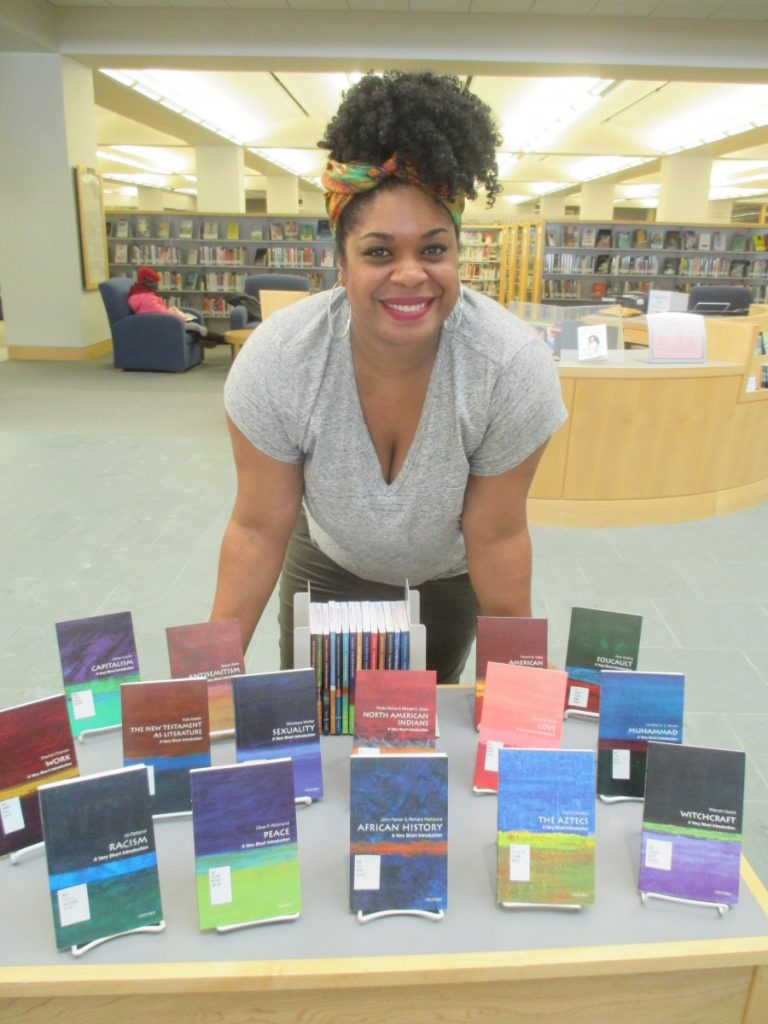 woman hovering over a table of books