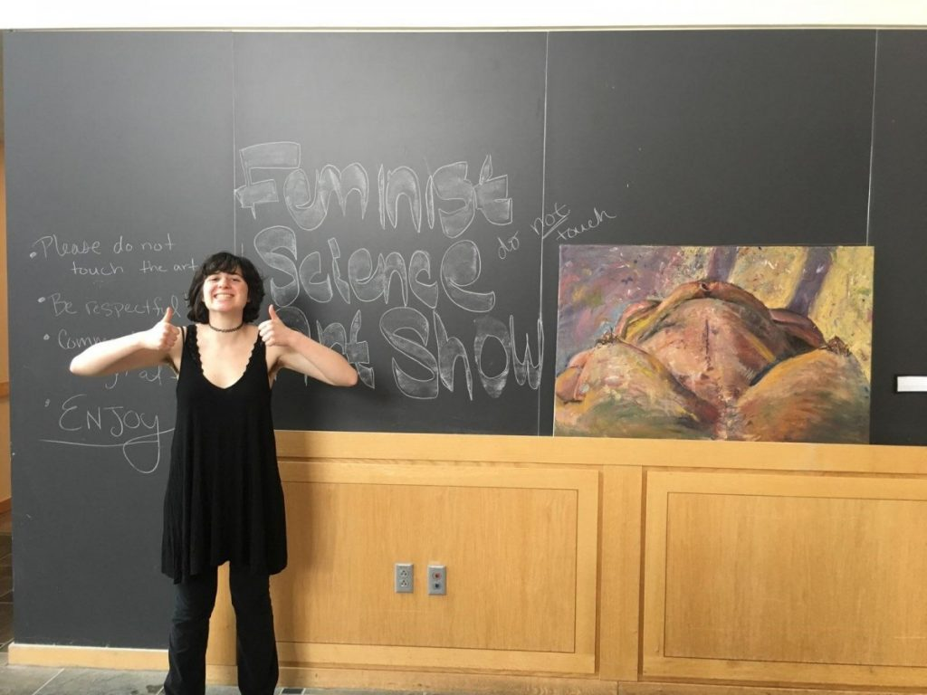 a woman posing in front of a blackboard