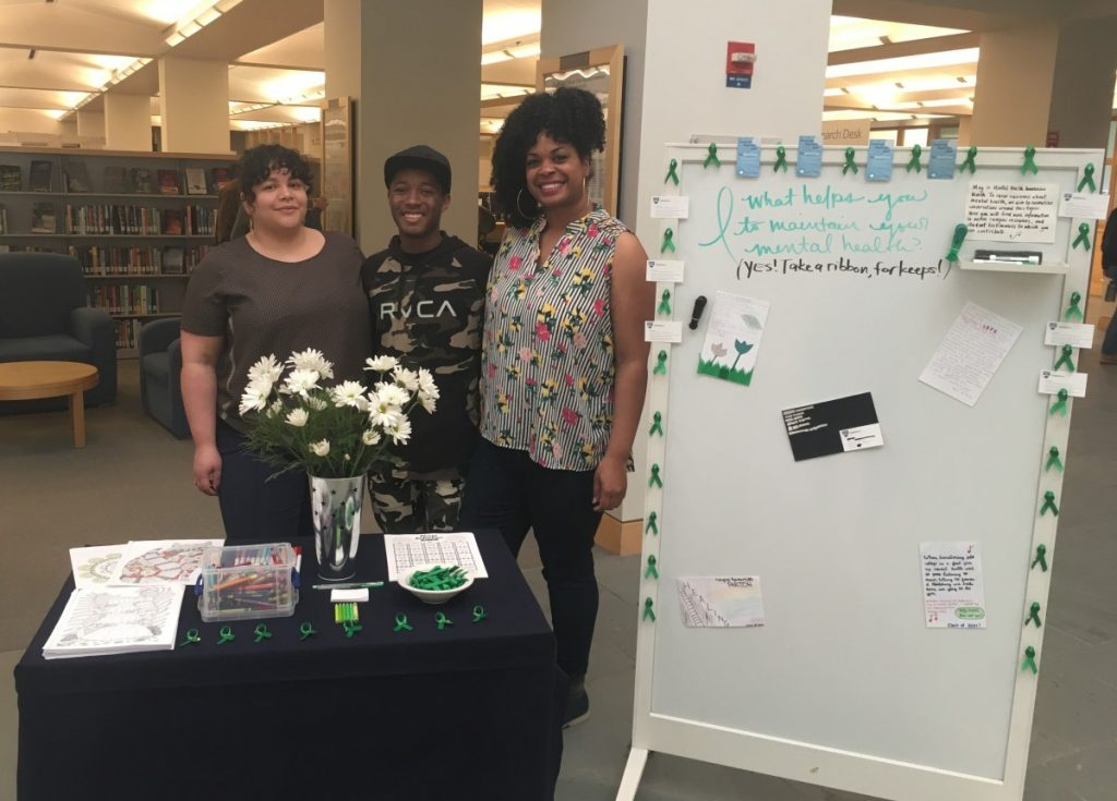 Professor Raquel Albarrán, Myles Maxie and Librarian Katrina Spencer pose with the Mental Health Awareness Month Display.