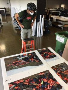 Darren Ell standing on a short ladder inspecting the colors and quality of the triptych prints