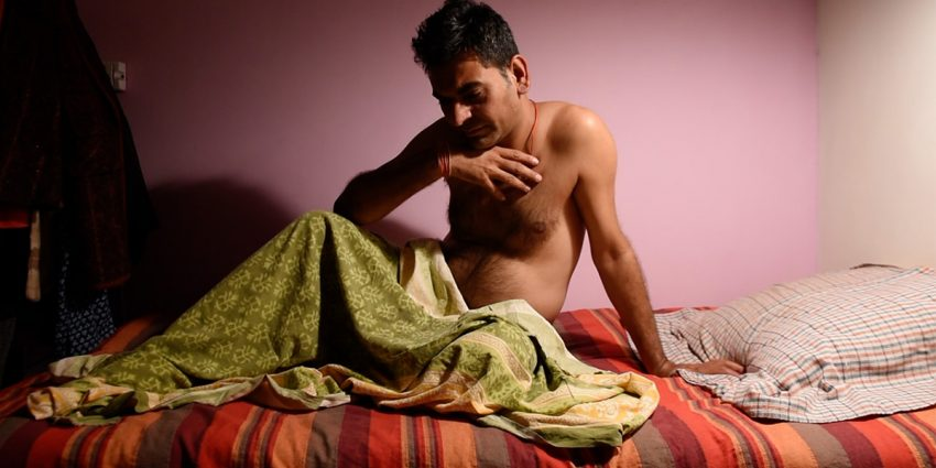 """An image still from Charan Singh's """"They Called it Love, But Was it Love"""" shows a man sitting upwards on a bed looking down in a pensive state. He is shirtless and has a green, patterned blanket draped over his lower body. He is set against a lavender colored wall."""
