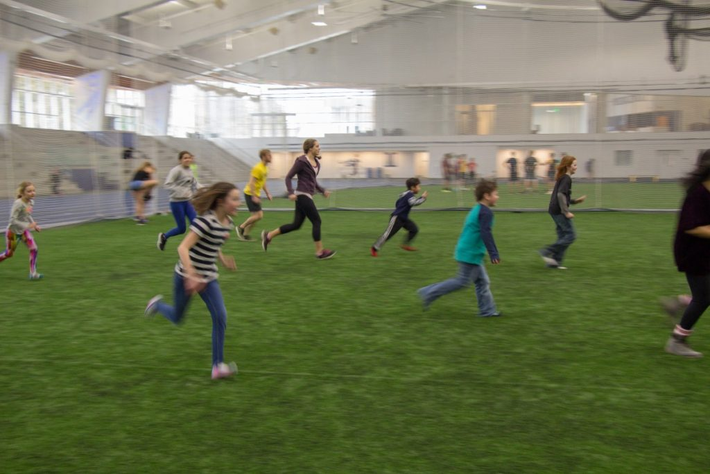 Kids playing soccer indoors