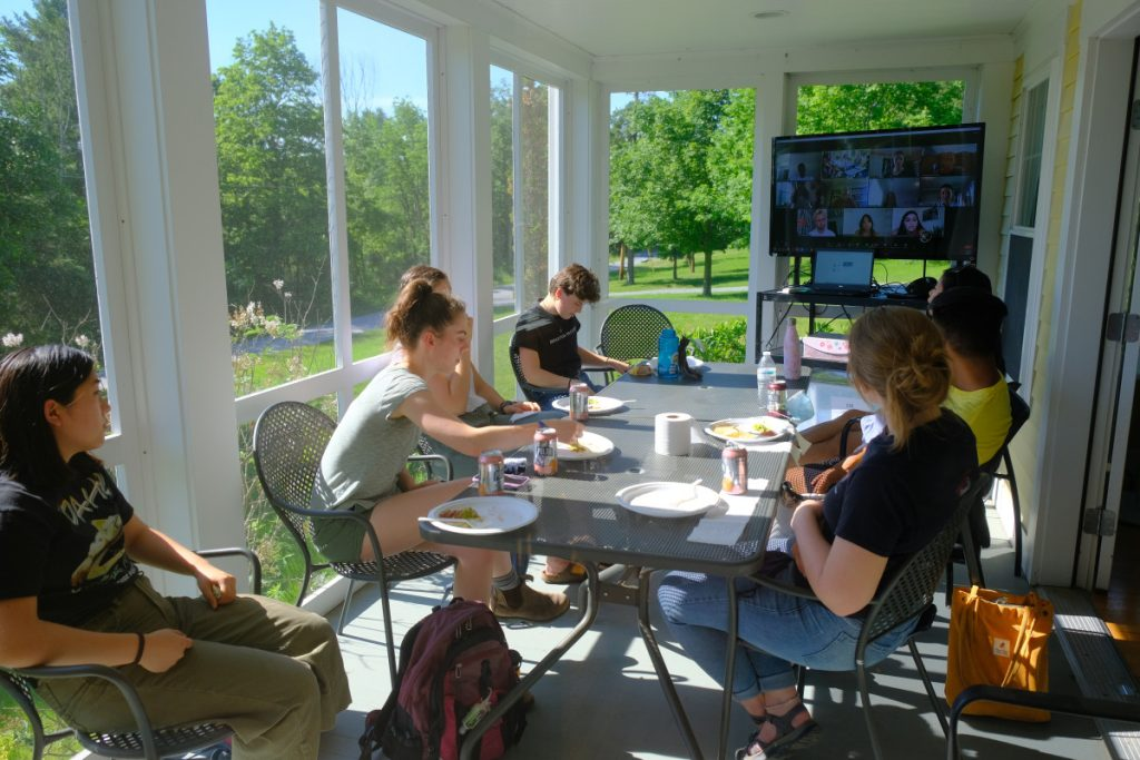 7 people sit around a table on a the screened-in porch of the Center for Community Engagement. They are sitting so that they can view a large TV which shows a Zoom screen where other members have joined them for a meeting.