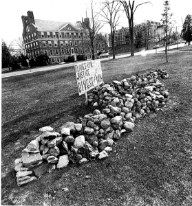 """A sign stood next to the wall, reading, """"Flames for Justice. Divest Now."""""""