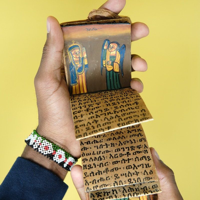Hands holding an Ethiopian Coptic prayer book open against a yellow background